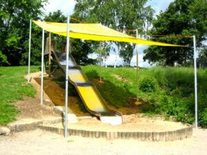 Ein gelbes Sonnensegel schattiert eine Hangrutschbahn auf einem Spielplatz.