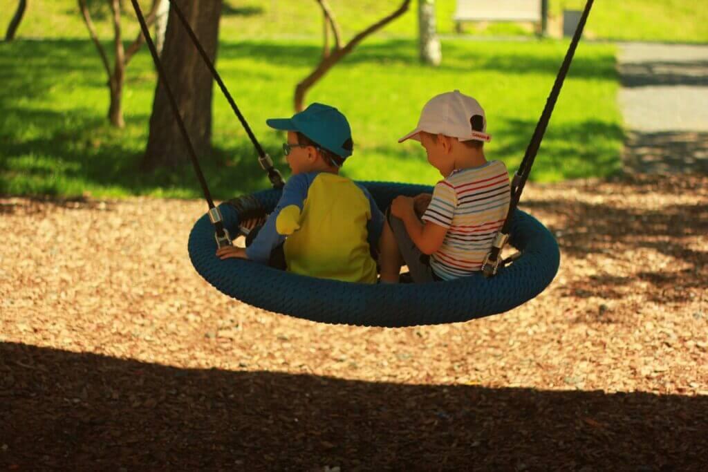 Zwei Kinder sitzen in einer Nestschaukel auf einem Spielplatz.